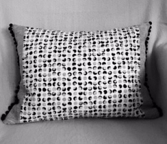 Stylish cushion with pom pom trim